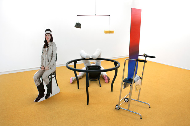 KATI HECK Mahler, Maler, Brad und Du (GrundLagenForschung), 2016 table, chair, Brad Pitt figure (polyurethane, synthetic hair, fabric, polyester filling)photographic cut-out of the artist on wooden structuremobile (stone, sponge, iron bar and cable)Gustav Mahler figure (walker, oil paint on mirror, vacuum-packed bags of peeled potatoes and Polder earth, papier mache, conductor rod, tuning-fork, bottle of milk) 271 x 320 x 253 cm