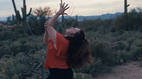 Yvonne Montoya dancing in the Sonoran Desert in a burnt orange shirt surrounded by saguaros.