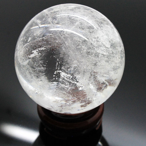 Clear quartz crystal sphere with wooden stand