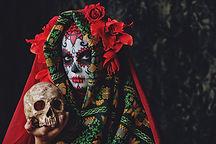 Calavera Catrina holding a skull over da