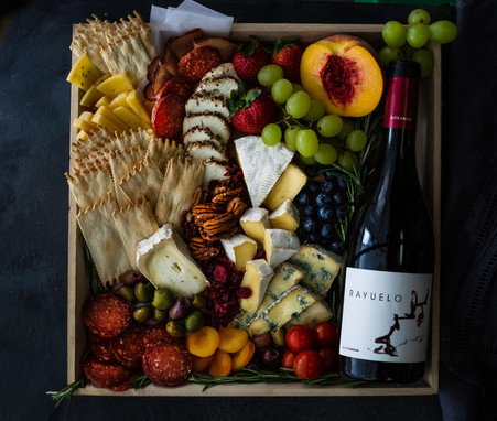 Food photography of gourmet cheese and fruit gift basket