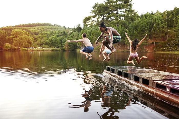 Kinder springen in den See