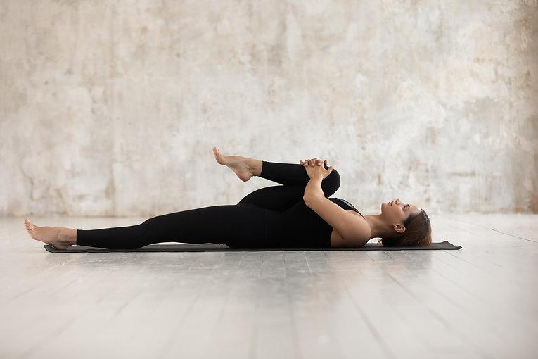 Woman wear black sport clothes lying on