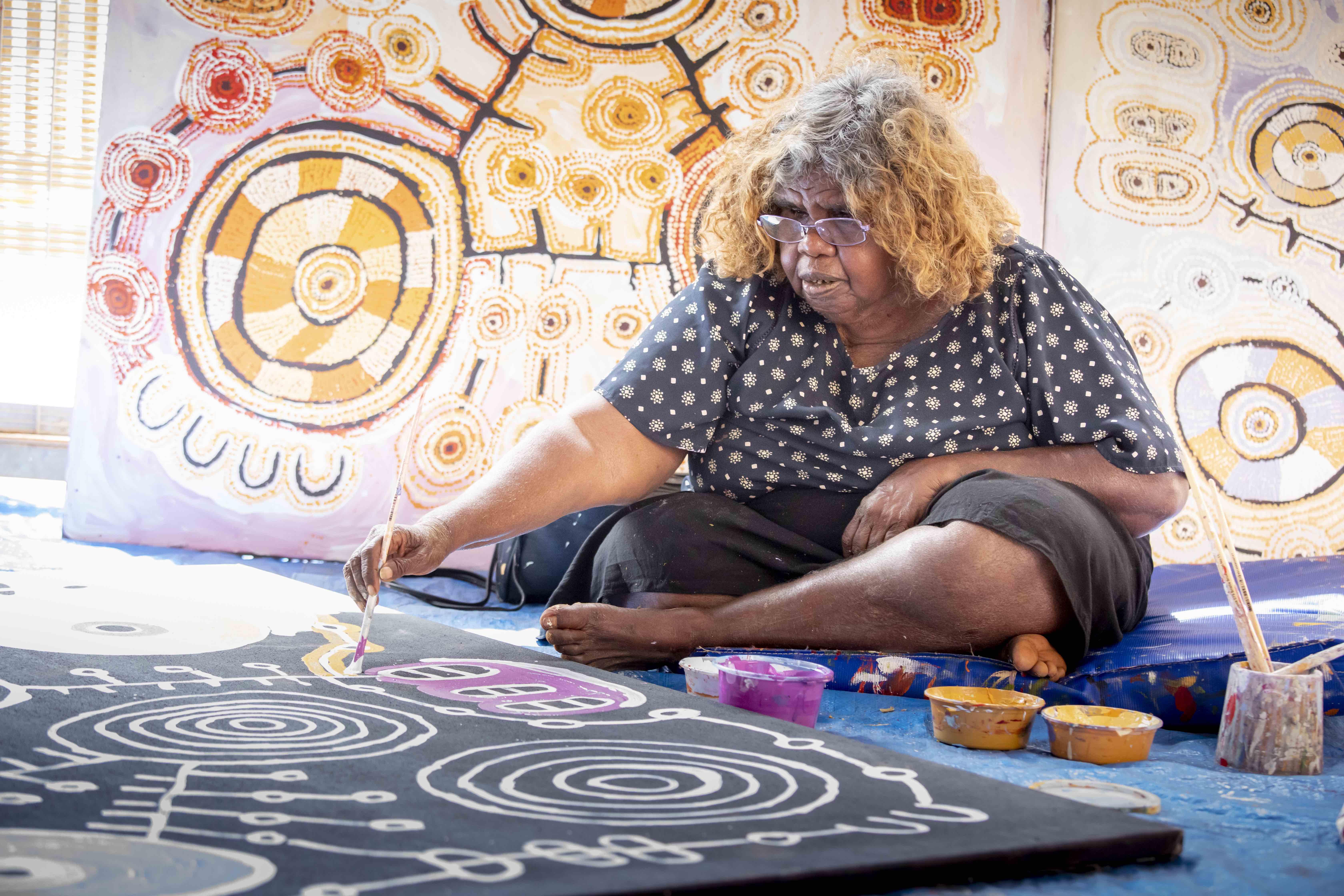 Tuppy Ngintja Goodwin working in the Mimili Maku Arts studio, photo: Meg Hansen