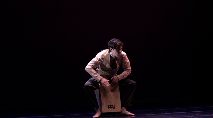 Jake playing cajon and dancing in his original piece Inside/Outside as part of Wayne State University's 2017 December Dance Concert.