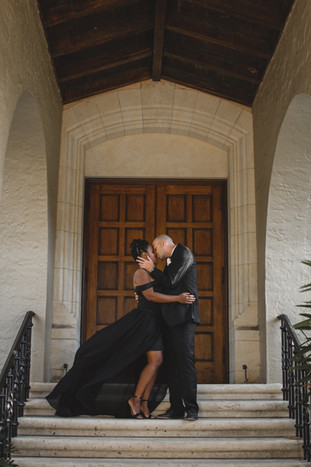 couple kissing on stairs in front of wooden door