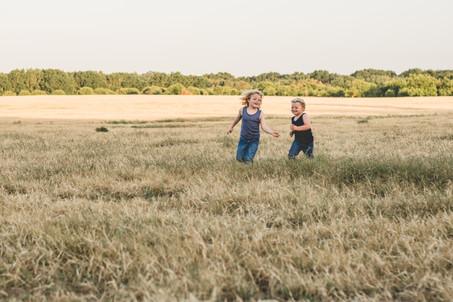 little boys running in a field