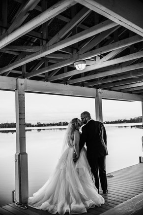 bride and groom kissing on a boat dock