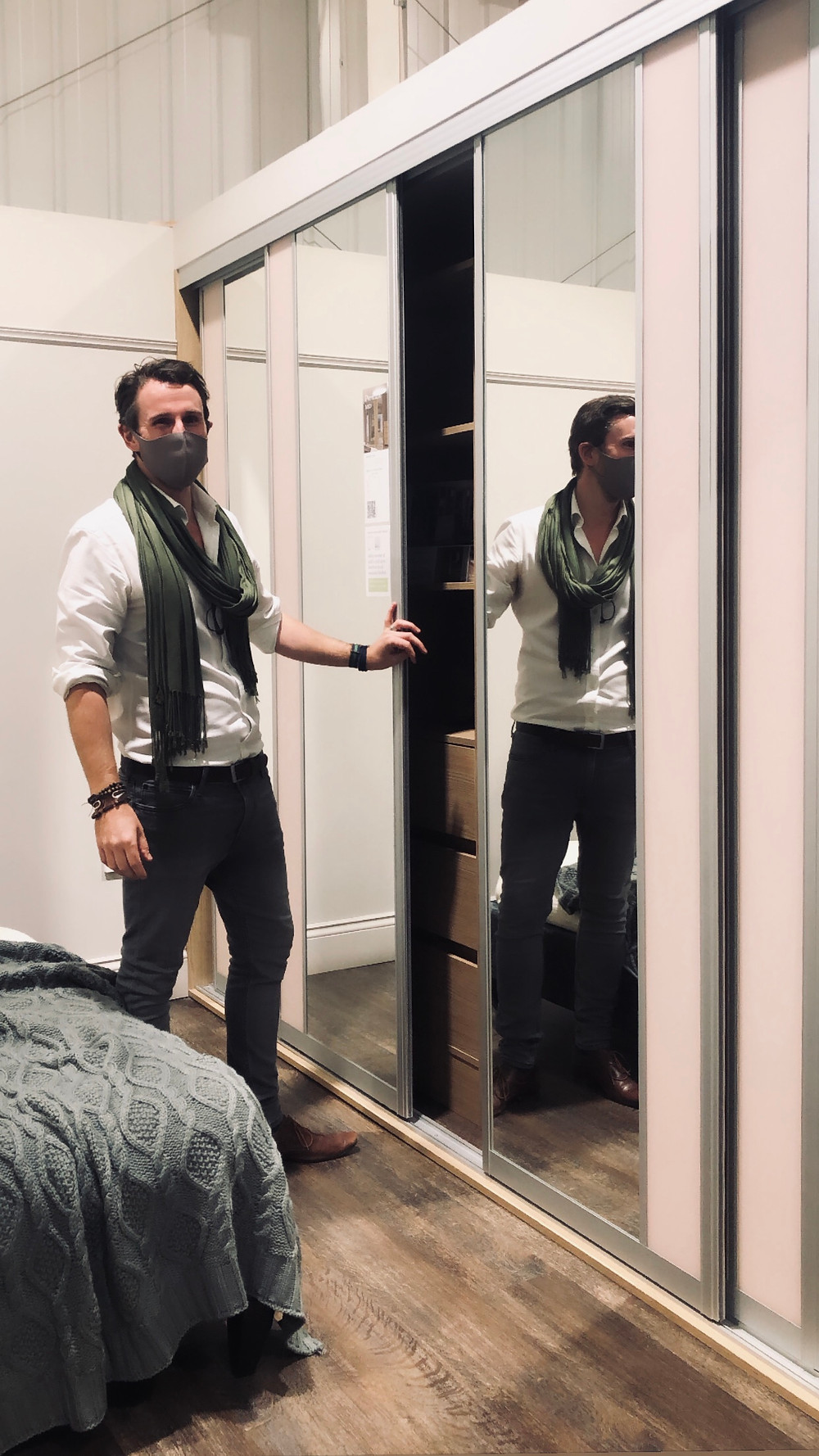 Image shows lead designer in green scarf opening sliding wardrobe