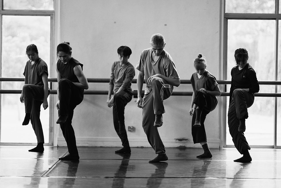 Background image of 6 dancers in a line, balancing on one leg with the other knee lifted high.