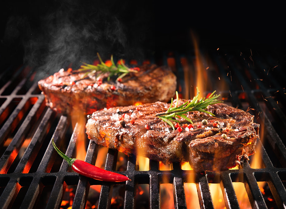 Beef steaks sizzling on the grill with f