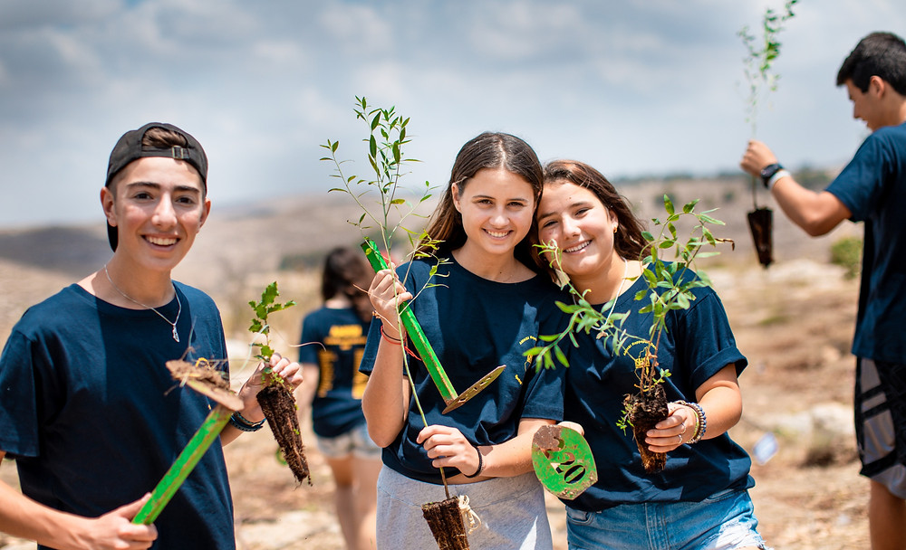 An Israeli boy and two girls holding up tree saplings and small hoes