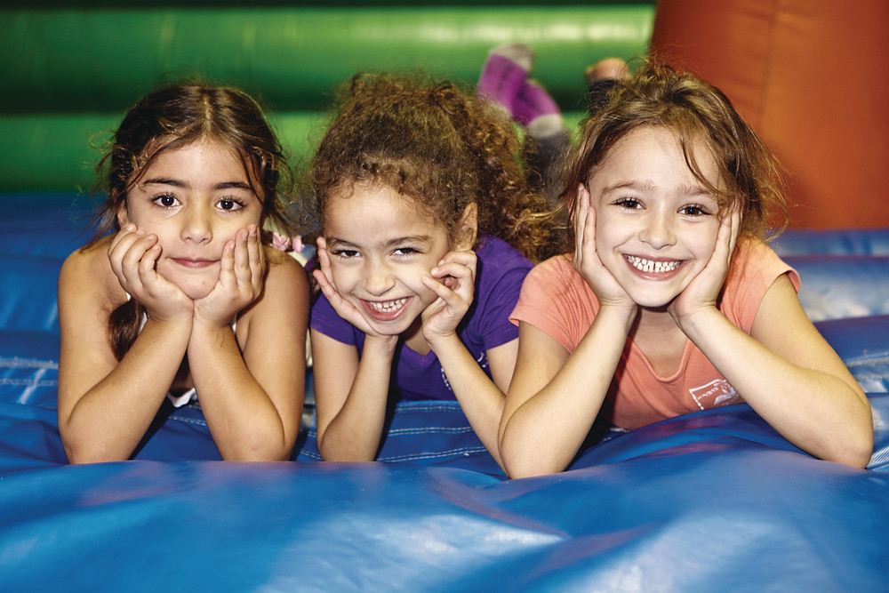 Three little Israeli girls laying on a blow up bouncing house
