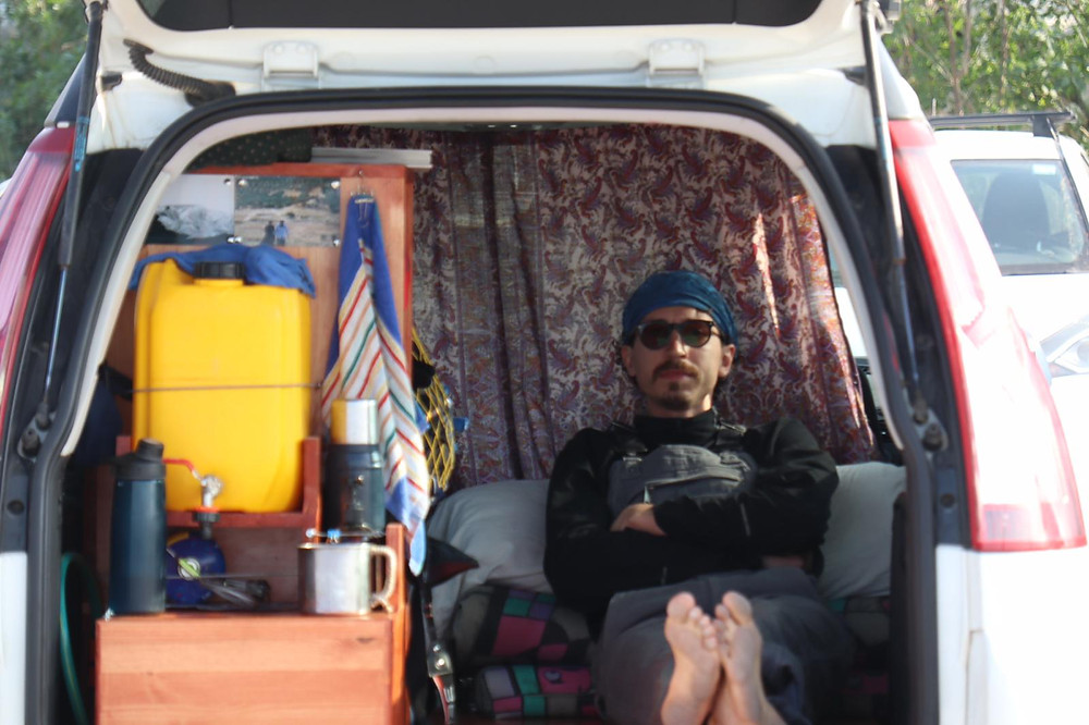 #Meet_the_Oleh: Nikita Smelyanskiy laying in the back of his van on a blanket with storage containers next to him