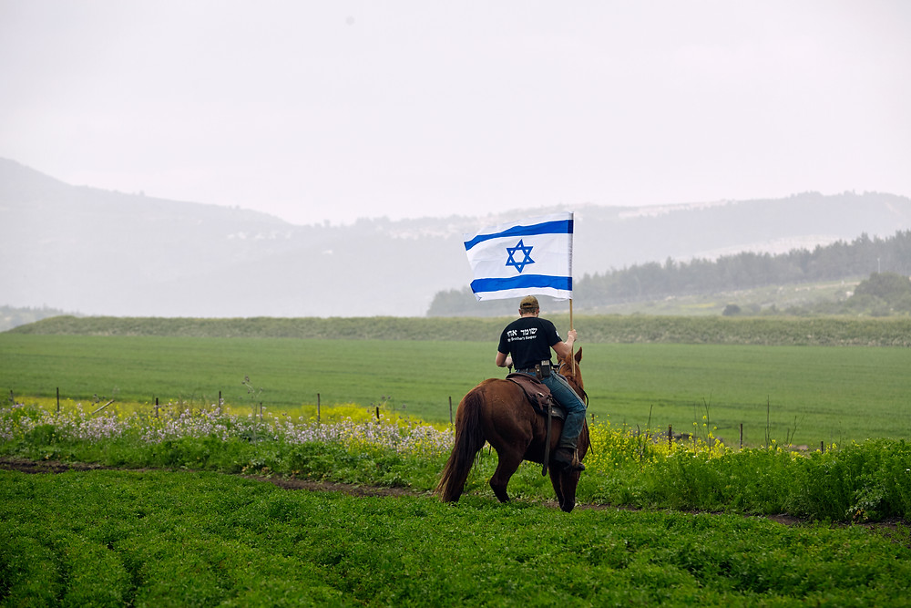 An Israeli farmer on a horse surveying his fields holding an Israeli flag