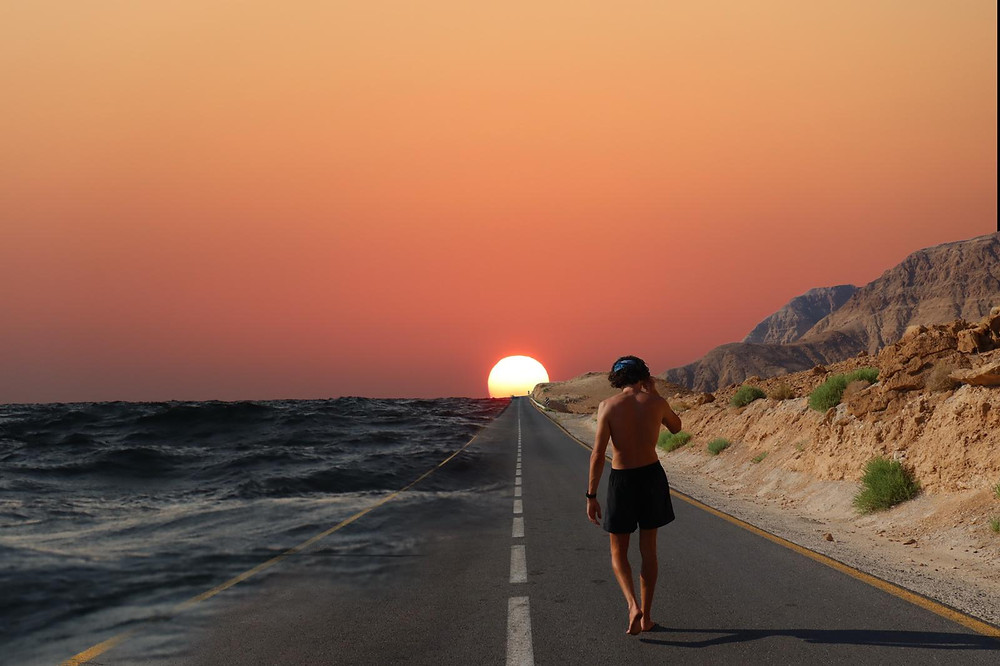 A man walking along an empty road towards the setting sun with the desert to the right and the sea to the left