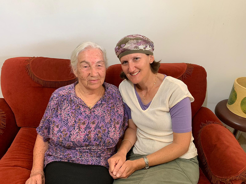A woman Holocaust survivor sitting on a red couch next to a middle ages woman