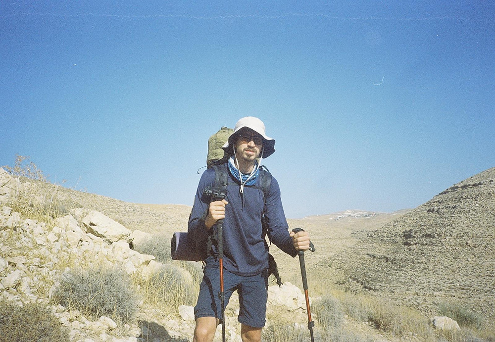 Oleh Nikita Smelyanskiy holding walking sticks in each hand, wearing a white hat, and large backpack outside