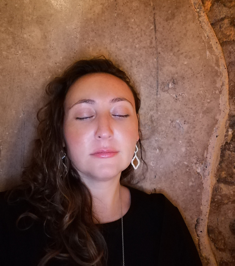 Oleh Kaley Zeitouni leaning against a stone wall in the Kotel Tunnels