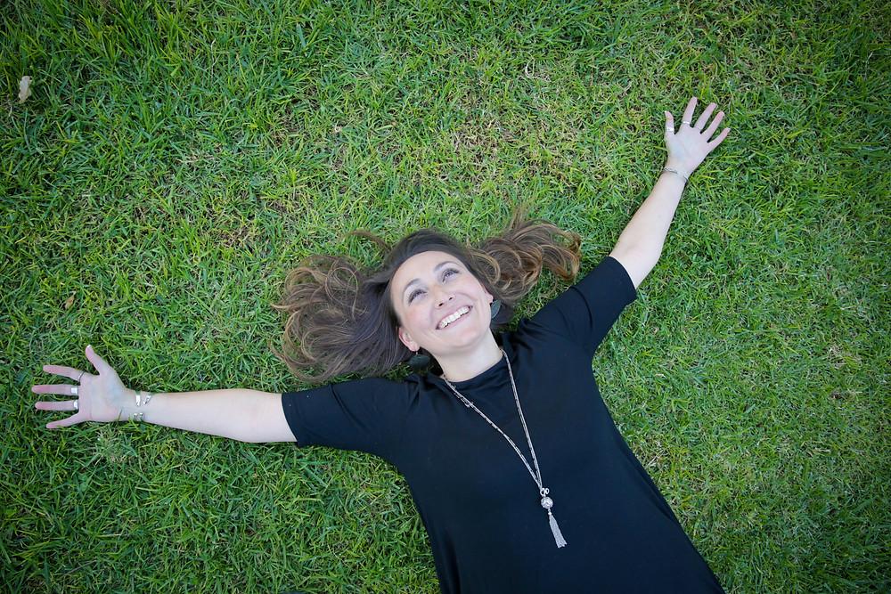 Oleh Kaley Zeitouni laying in a grass field in Jerusalem