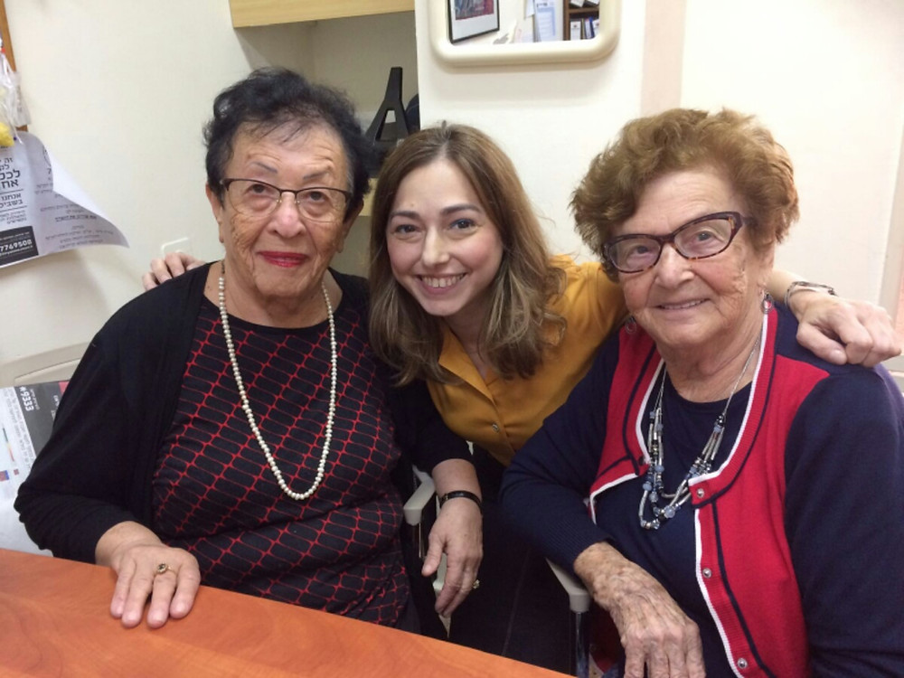 A young woman in between two women Holocaust survivors