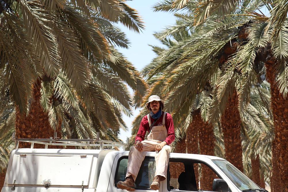 Oleh Nikita Smelyanskiy sitting on top of his white van with date palms behind him