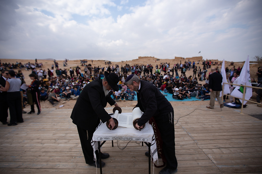 Two men rolling up a Torah scroll on a table on Masada in front of a crowd