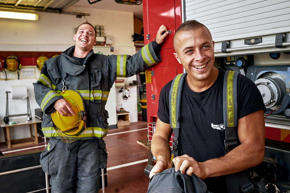 Two Israeli firefighters in their uniforms laughing inside a fire station