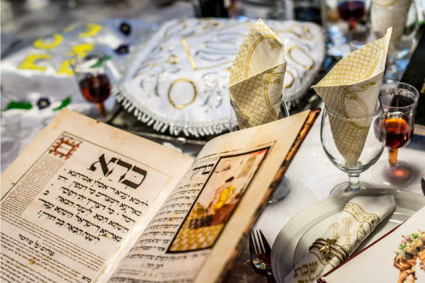 An open hagaddah is read over a table with matza is a Passover tradition