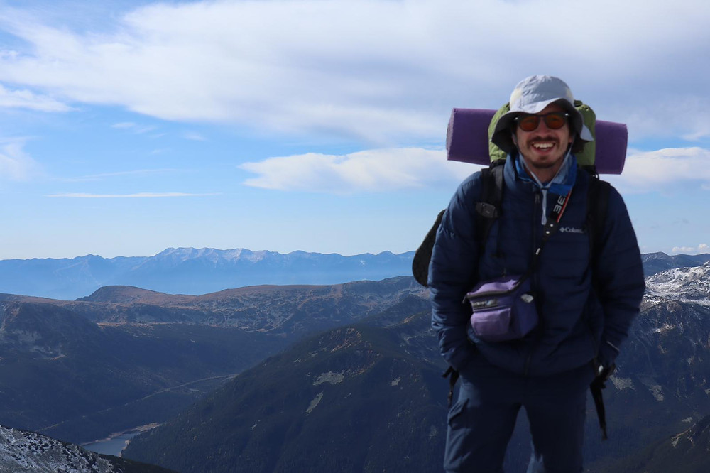 Oleh Nikita Smelyanskiy standing on top of a mountain smiling with a backpack, sleeping mat, and white hat