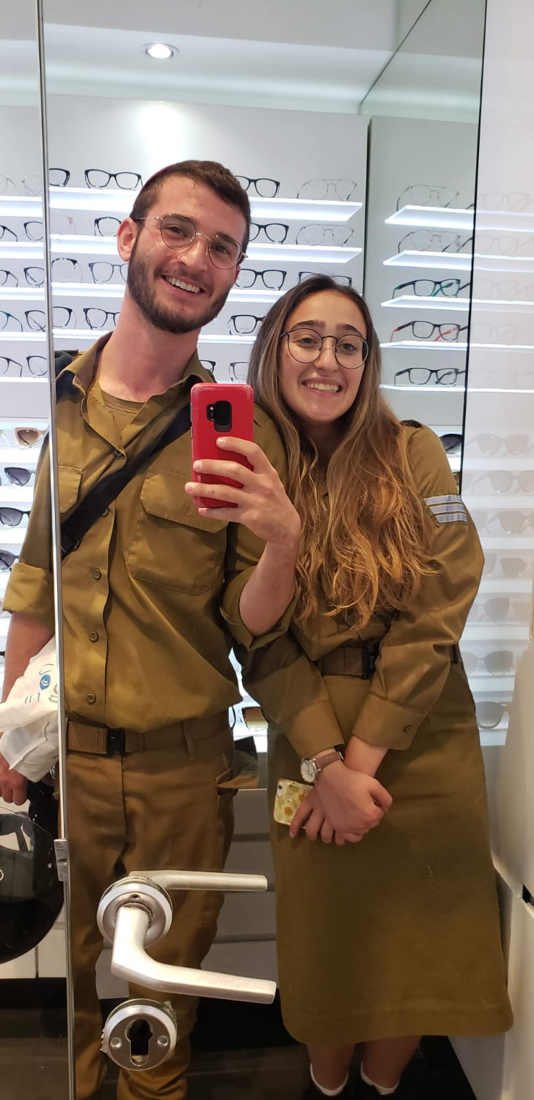 Oleh Sophie Knop trying on glasses at a store with a friend in their IDF uniforms