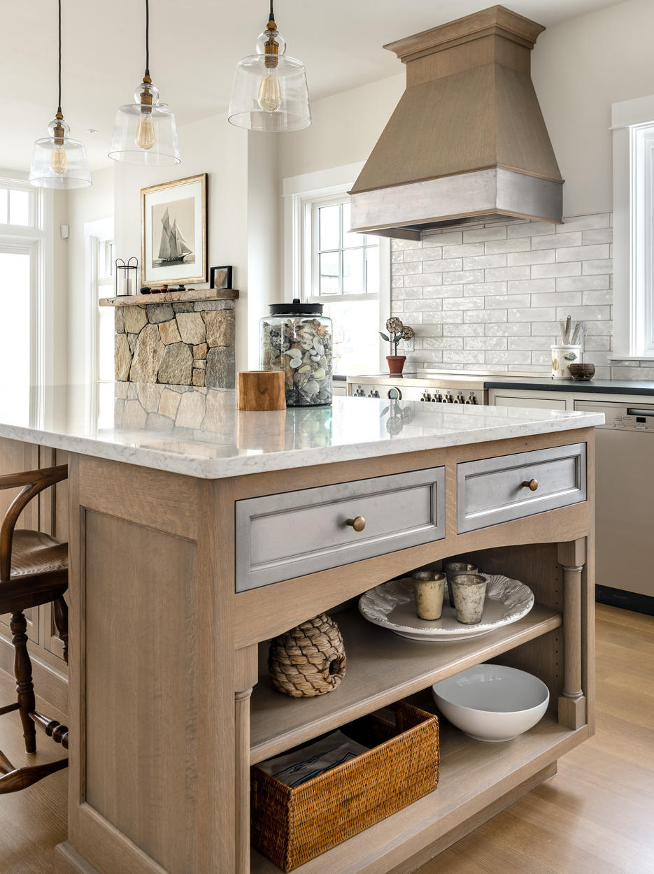 """The island and hood feature weathered quarter sawn oak with a stain that reflects the warm gray tones found in driftwood. This adds warmth and texture to the room. A painted pewter """"Metal Fusion"""" finish accents the hood and island drawers. This will patina over time creating a wonderful richness, as well as the natural bronze that we selected."""