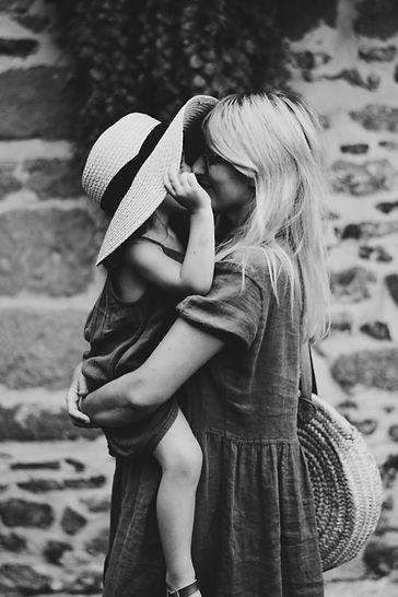 femmes blonde aux cheveux longs qui porte un enfant dans ses bras avec un chapeau, robes d'été