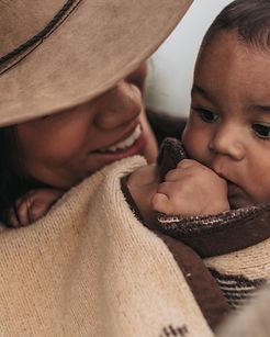 femme avec un chapeau portant un bébé avec une couverture