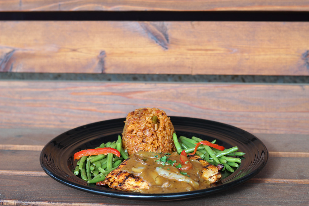 An image of Bayou Smothered Chicken on a black plate