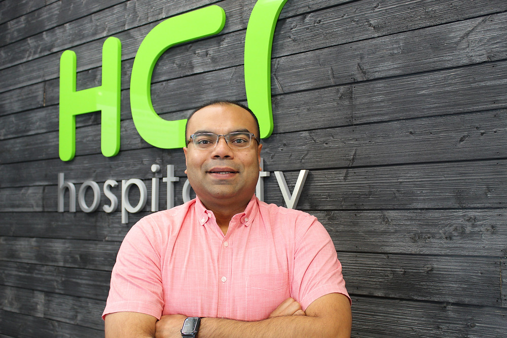 An image of Munish Babbar, the HCI Chief Operations Officer standing in front of a grey wall with the Green HCI logo.