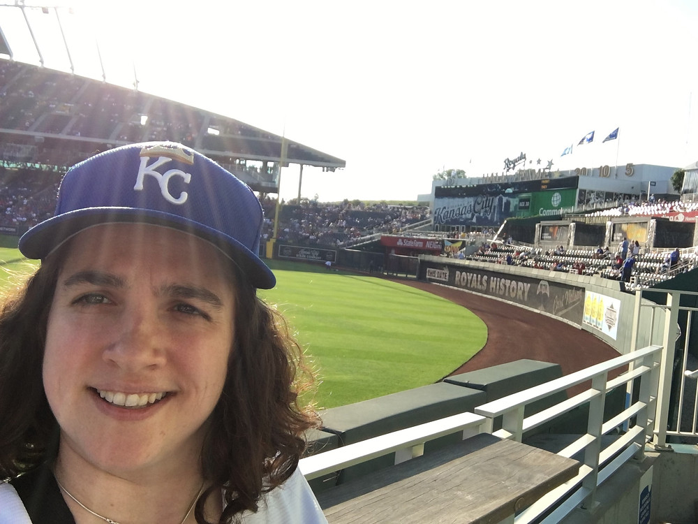 A photo of Emily in a KC Royals baseball hat at Kaufmann Stadium