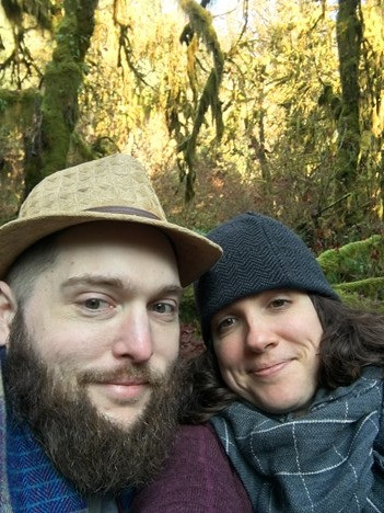 A photo of a man (Aaron) and woman (Emily) in the woods
