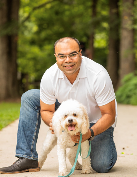 An image of Munish standing on a path with his Cavachon dog named Toffee