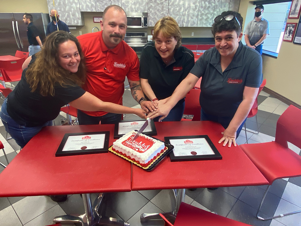 Crystal Kosnjek (Millard), Greg Elchert (Killeen), Steph Gallant (Temple), Donna Lawson (Burlington) cutting a celebratory cake