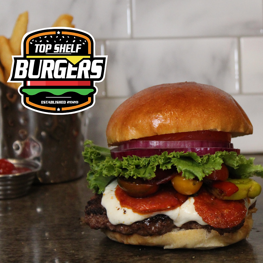 """Image of the """"Godfather Burger"""" - a burger patty stacked with lettuce, tomato, onion, pickles, mayo, fresh mozzarella marinated veggies and pepperoni on a brioche bun"""