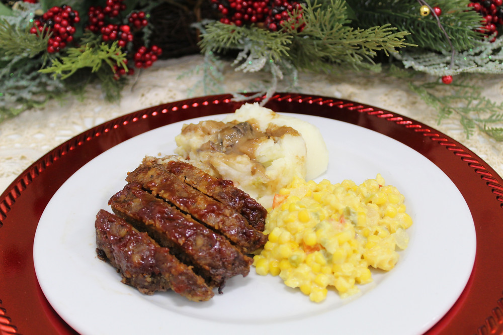 Meatloaf, served with mashed potatoes and brown gravy with a side of corn.