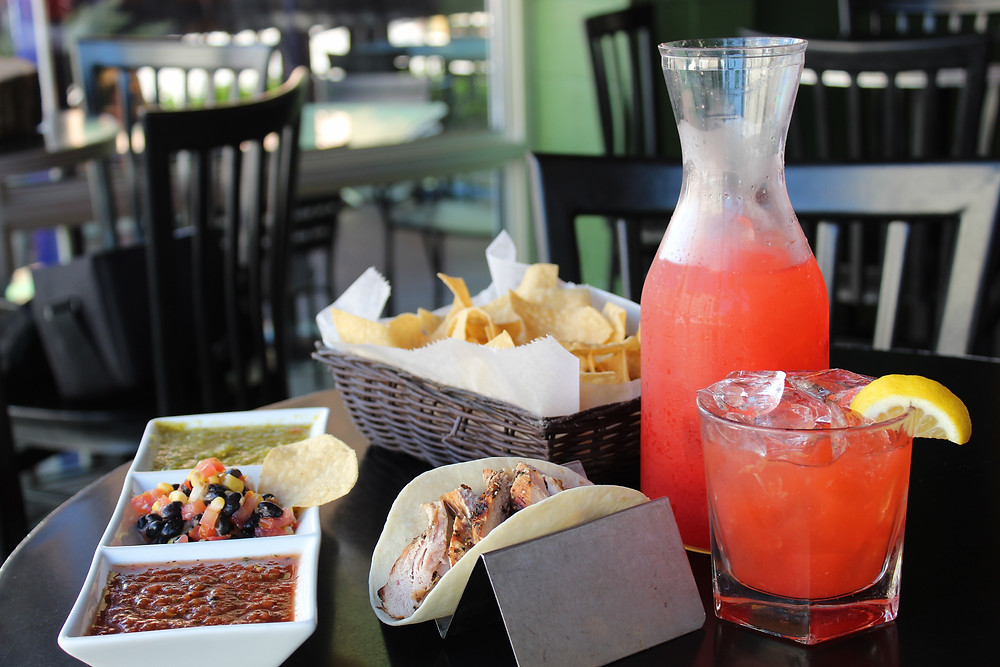 A photo of Coco Bolos' trio sampler, taco, chips, and carafe drink offered during happy hour