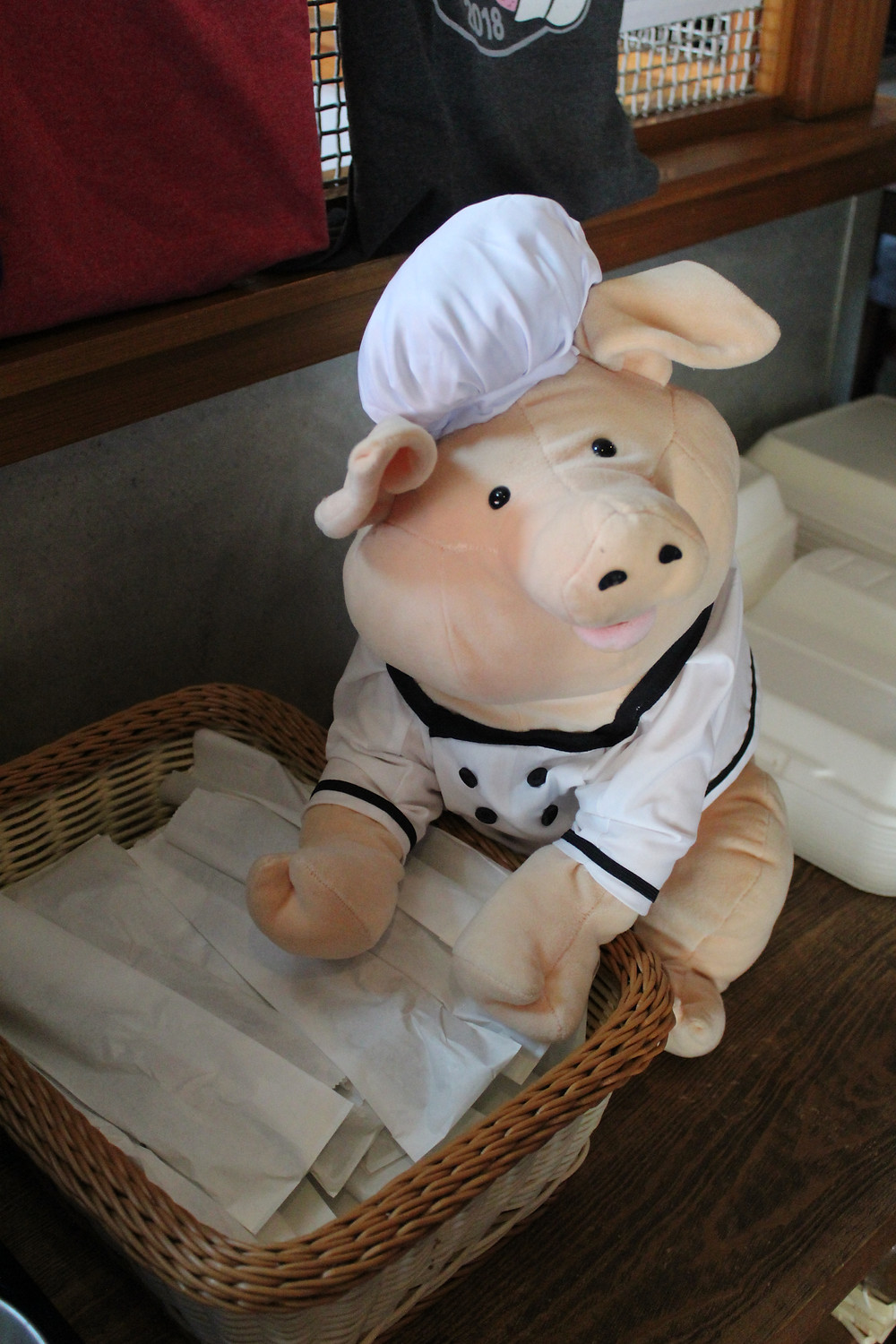 A stuffed pig posed next to wrapped silverware