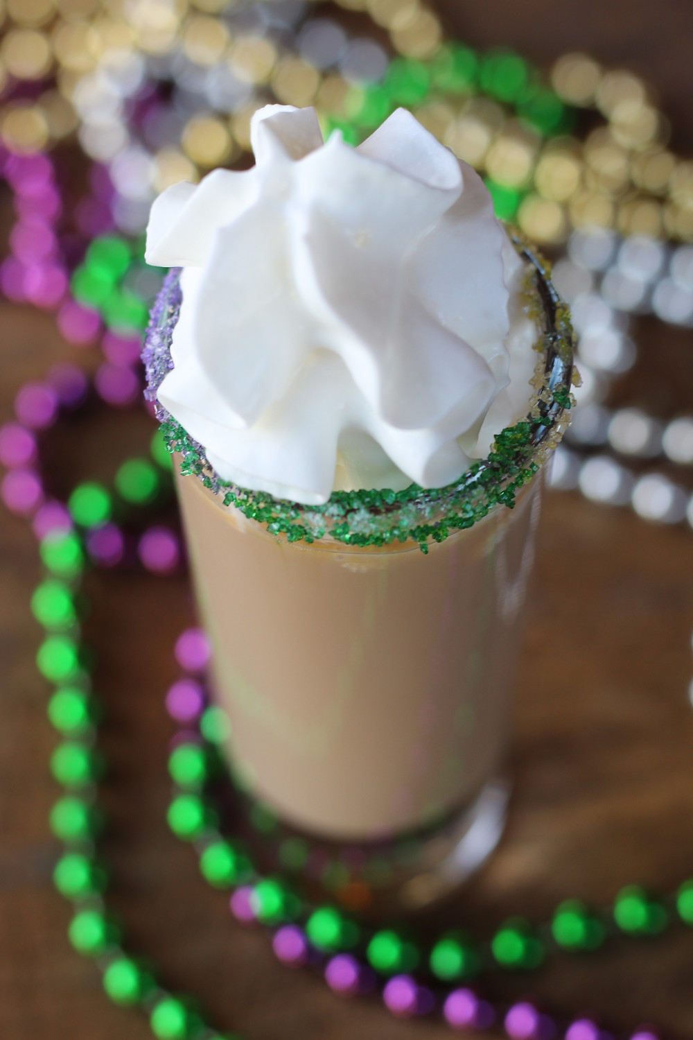 An image of a King Cake Shot, topped with whipped cream