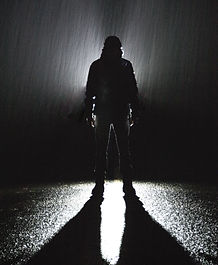Silhouette of man in rain at night