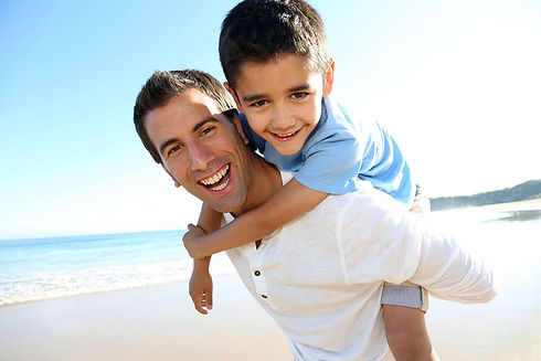 man-carrying-male-child-at-beach.jpg