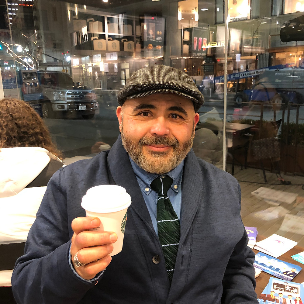Ted wears a dark gray newsboy cap while dressed in a dark gray button front jacket, wearing a blue button-down shirt with a green horizontal striped tie and holding a small cup of coffee in a shop in front of large glass windows.