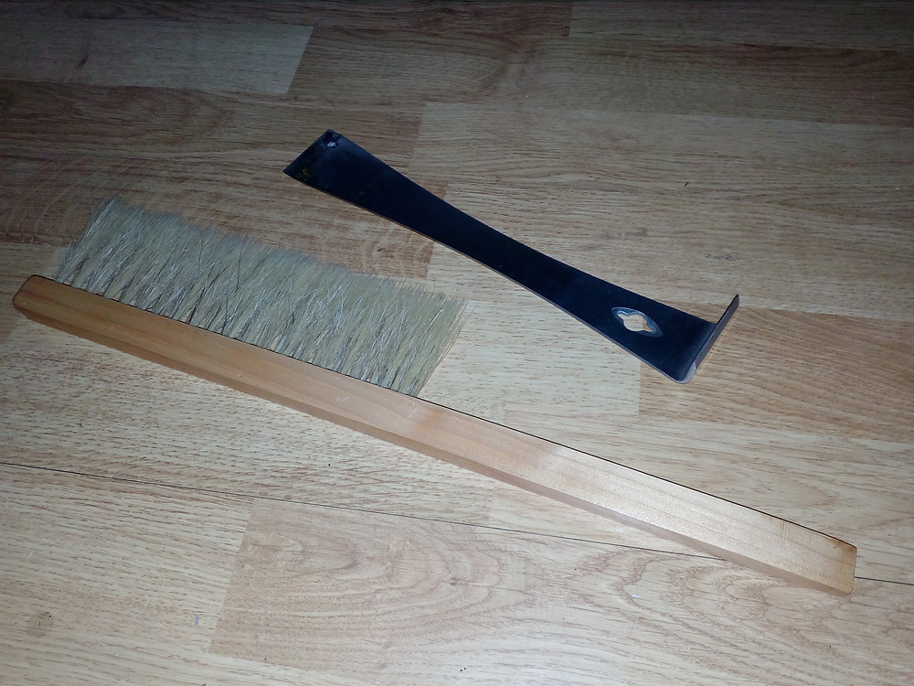 A bee brush (left hand side) and bee tool (right hand side)