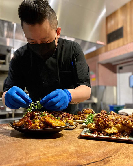 Chef David Puccinelli of WingSlut adding microgreens to a plate of chicken wings.
